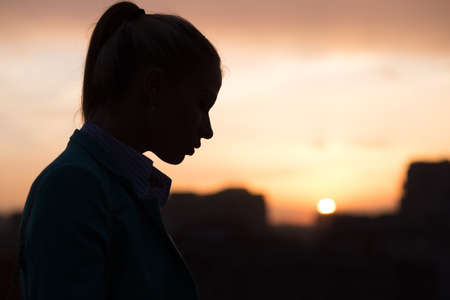 roof profile: silhouette of a girl on the roof at sunset in the city