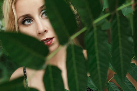 single animal: Portrait of young beautiful woman on green leafs back