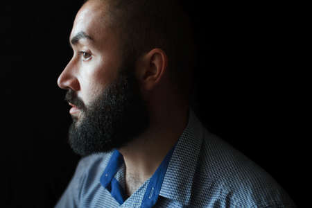 male face profile: A man with a beard in a profile on a black background