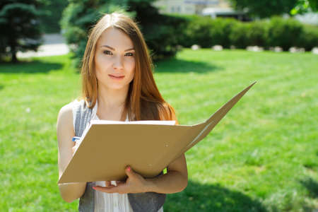 girl studying: Business woman with folder and paper notebook standing in the park on conference Stock Photo