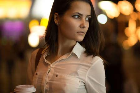 Mooi meisje in de nacht stad koffie te drinken. Stadslichten. Stockfoto