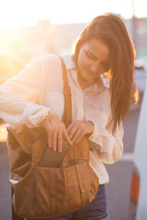 きれいな女の子は、袋に携帯電話を入れてください。夕日の美しい柔らかな光。