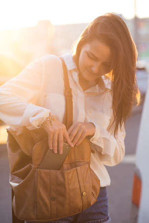 Pretty girl put the phone in bag. Beautiful soft light at sunset. Stock Photo