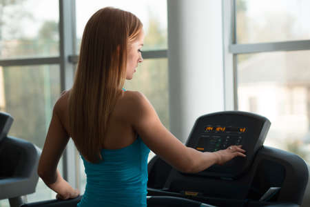 click button: Sport woman staying on a treadmill and click button Stock Photo