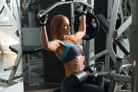 latissimus: Athletic woman doing exercises on training apparatus in gym Stock Photo
