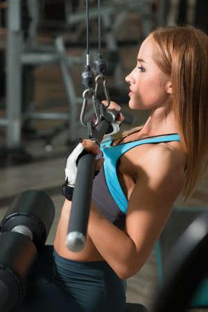 latissimus: Athletic woman doing exercises on training apparatus Stock Photo
