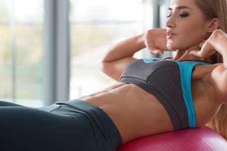 muscle training: Starke nette Frau macht Fitness-Übungen auf fitball Lizenzfreie Bilder