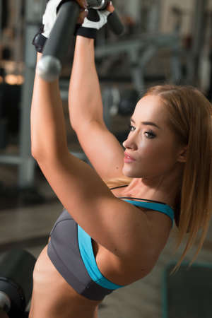 latissimus: Strong woman doing exercises in gym