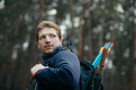 bowstring: Man go with hunter bow in forest