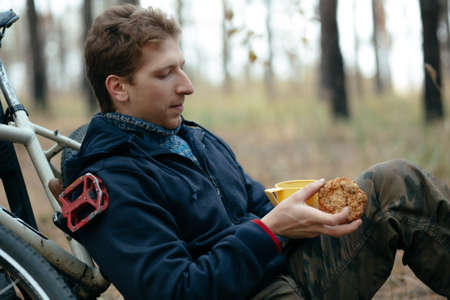 snacking: Man tourist with bike sitting and snacking in forest Stock Photo