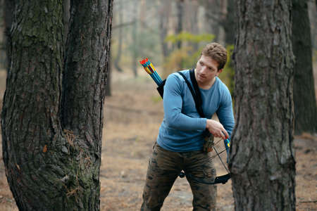 bowstring: Man with hunter bow goes through the wood Stock Photo