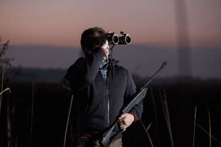 hunter man: Hunter man with rifle see in binocular in field in evening
