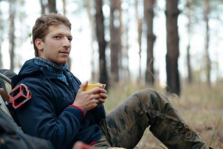 nosh: Man tourist with bicycle sitting and snacking in forest