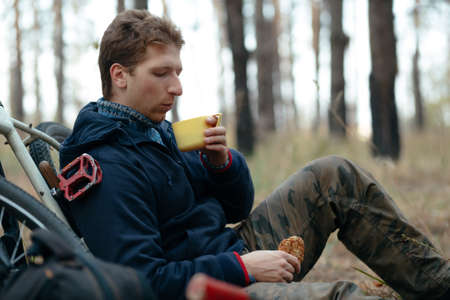 snacking: Tourist man with bike sitting and snacking in forest