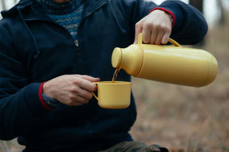 nosh: Tourist man sitting and pours herself tea in forest. Cropped photo.