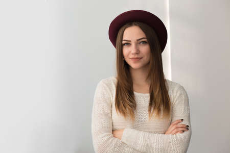 preppy: Fashionadle woman in hat. White wall background.