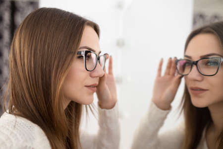 preppy: Girl dress glasses for good vision in front of the mirror Stock Photo