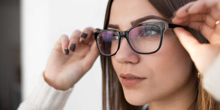preppy: Woman try on glasses for good vision Stock Photo