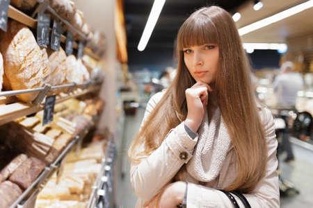 choosing: Woman choosing bread at supermarket