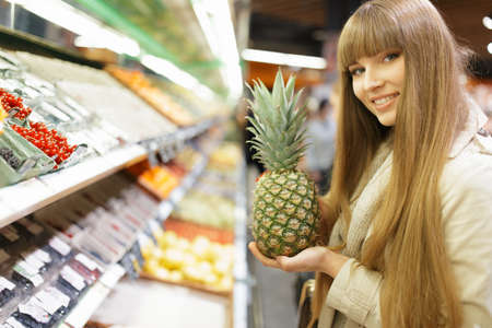forelock: Woman choosing fruits at supermarket and holding pineapple
