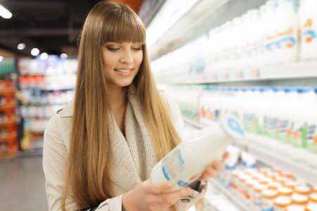 choosing: Woman choosing dairy products at supermarket Stock Photo