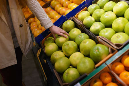 Female hand picks Citrus Sweetie at supermarket