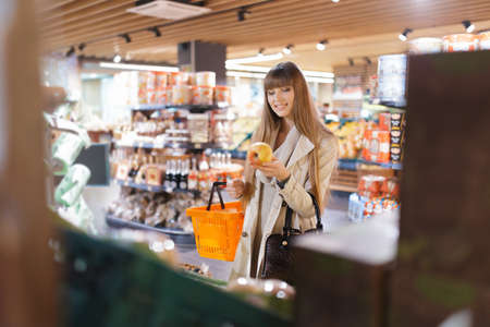 forelock: Woman choosing apples at supermarket and holding it