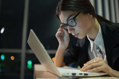 slog: Businesswoman working at a laptop late at night in office Stock Photo