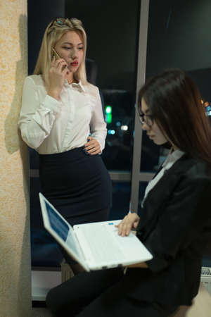 slog: Two businesswomen working in her office late at night