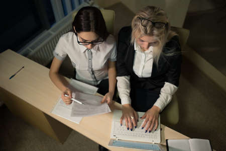 slog: Two businesswomen working with a laptop in office late at night