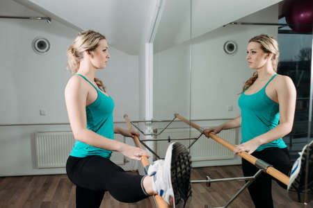 limbering: Woman doing stretching near barre in fitness center Stock Photo