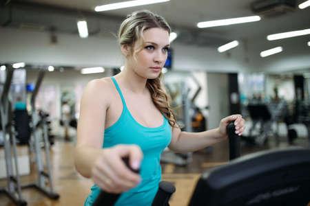 elliptical: Aerobics. Woman doing exercises on elliptical walker at fitness gym. Stock Photo