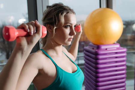deltoid: Beautiful sportswoman doing exercise for deltoid with dumbbell in fitness center