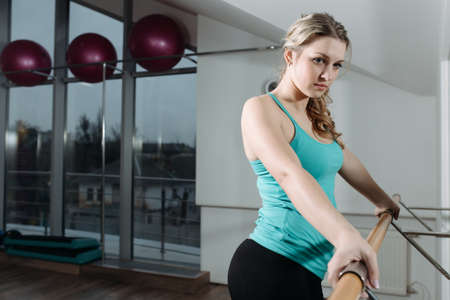 barre: Woman standing near barre in fitness center