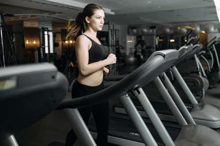 treadmill: Adult sport woman running on treadmill in gym Stock Photo