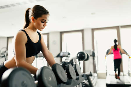only the biceps: Beautiful woman take a dumbbell in gym