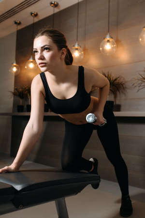 dorsi: Beautiful woman lifting dumbbell at bench in gym
