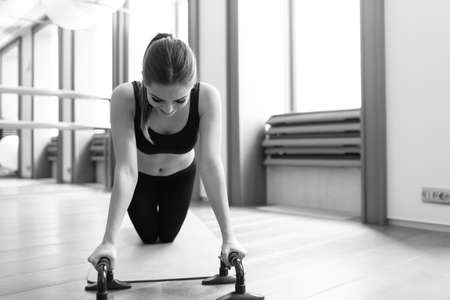 karemat: Woman doing push ups exercise. Powerful female exercising in health club.