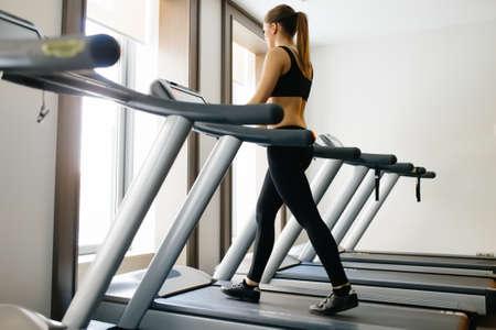 Adult sport woman walking on treadmill in gym
