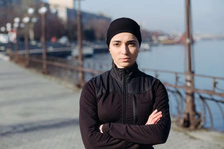 woman with camera: Portrait of athletic woman in city. She looks into the camera.