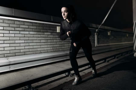 25 29 years: Woman running at nighttime on the roof
