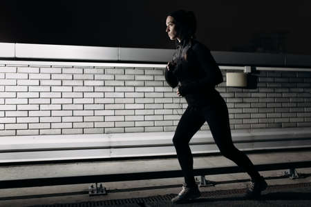25 29 years: Woman running at nighttime on the parking roof