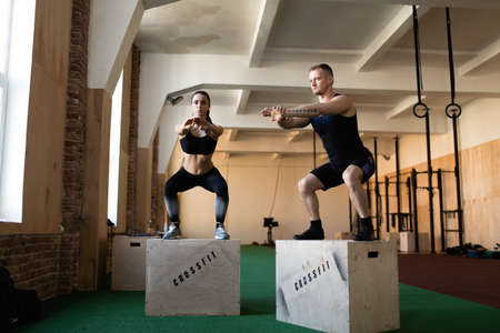 25 30 years women: Young athletes doing box jump in crossfit gym Stock Photo