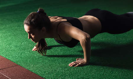 pushup: Woman doing push-up in gym Stock Photo
