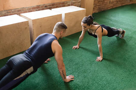 25 30 years women: Man and woman training together at the gym