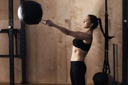 Vrouw lift gewicht bal in de sportschool Stockfoto