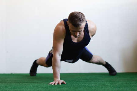 pushup: The athlete doing push-up in gym on a one hand