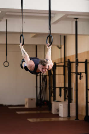 30 34 years: Caucasian athlete hanging on gymnastic rings Stock Photo
