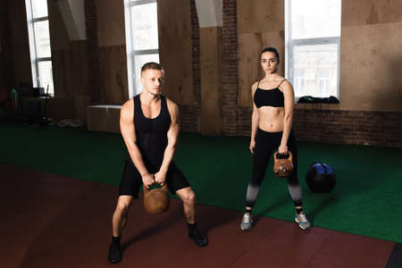 25 29 years: Man and woman training together at the gym. They press kettle bells.