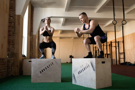 25 30 years women: CrossFit athletes doing box jumps Stock Photo